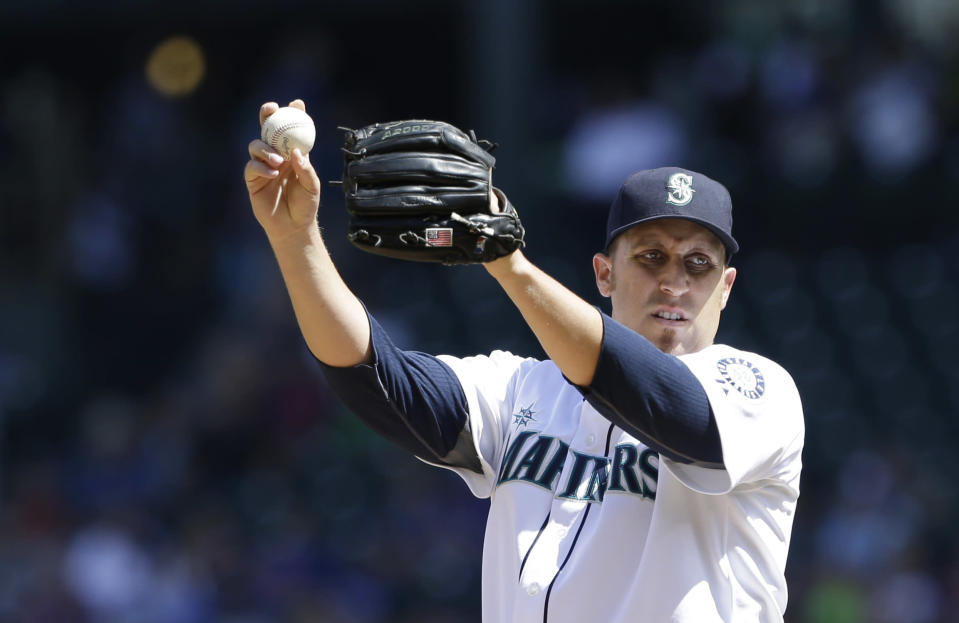 Seattle Mariners starting pitcher Aaron Harang stretches after giving up a hit to the Toronto Blue Jays in the second inning of a baseball game on Wednesday, Aug. 7, 2013, in Seattle. (AP Photo/Elaine Thompson)