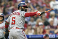Washington Nationals'Josh Harrison (5) gestures at home plate with Gerardo Parra's bat after he scored on an RBI-single by Parra during the fourth inning of a baseball game against the Philadelphia Phillies, Monday, July 26, 2021, in Philadelphia. (AP Photo/Laurence Kesterson)
