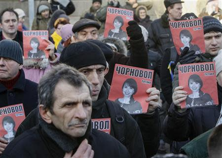 Protesters hold pictures of journalist Chornovil, who was beaten just hours after publishing an article on the assets of top government officials, during a protest rally in front of Ukrainian Ministry of Internal Affairs in Kiev