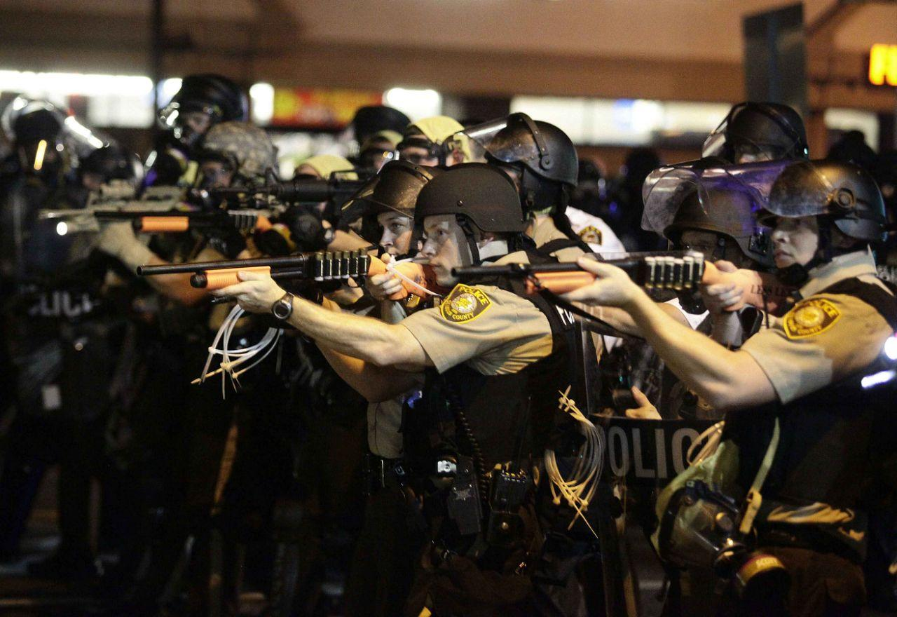 <p>Police officers point their weapons at demonstrators protesting against the shooting death of Michael Brown in Ferguson, Missouri August 18, 2014. Police fired tear gas and stun grenades at protesters on Monday after days of unrest sparked by the fatal shooting of unarmed black teenager Michael Brown by a white policeman. (Joshua Lott/Reuters) </p>