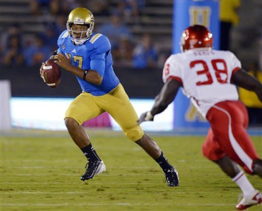 UCLA quarterback Brett Hundley, left, runs the ball as Houston defensive back Steven Aikens defends during the first half of an NCAA college football game, Saturday, Sept. 15, 2012, in Pasadena, Calif. (AP Photo/Mark J. Terrill)