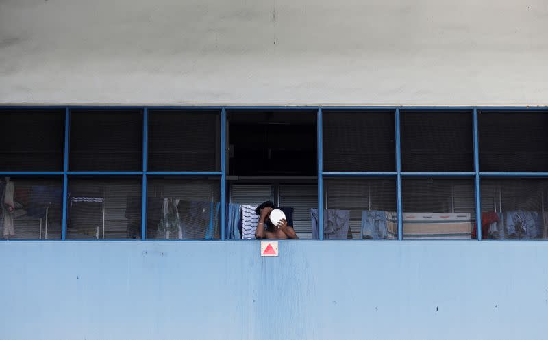 A migrant worker living in a factory-converted dormitory looks into a mirror as he serves stay-home notice during the coronavirus disease (COVID-19) outbreak in Singapore