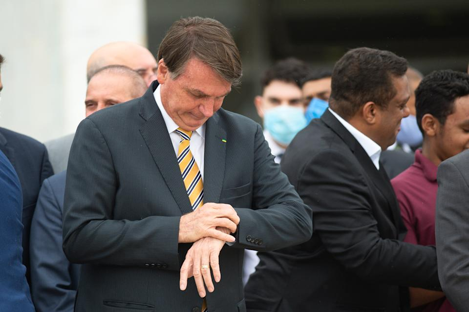 BRASILIA, BRAZIL - NOVEMBER 19: Jair Bolsonaro, President of Brazil, looks at the watch before Commemorates Brazilian Flag Day amidst the coronavirus (COVID-19) pandemic at the Planalto Palace on November 19, 2020 in Brasilia. Brazil has over 5.945,000 confirmed positive cases of Coronavirus and has over 167,455 deaths. (Photo by Andressa Anholete/Getty Images)