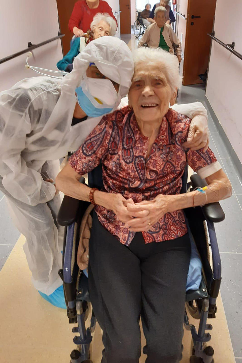 """In this photo taken on April 1, 2020, 103-year-old Ada Zanusso, poses with a nurse at the old people's home """"Maria Grazia"""" in Lessona, northern Italy, after recovering from Covid-19 infection. To recover from coronavirus infection, as she did, Zanusso recommends courage and faith, the same qualities that have served her well in her nearly 104 years on Earth.The new coronavirus causes mild or moderate symptoms for most people, but for some, especially older adults and people with existing health problems, it can cause more severe illness or death. (Residenza Maria Grazia Lessona via AP Photo)"""