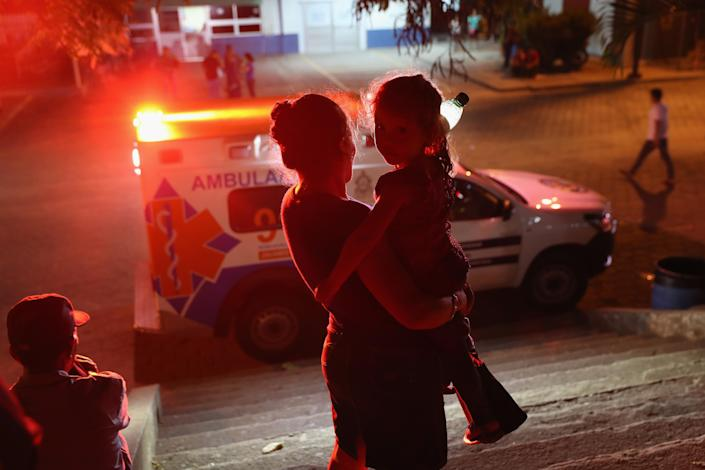 A mother and child watch an ambulance leaving a hospital on Aug. 17, 2017, in San Pedro Sula, Honduras. The city has some of the highest violence and murder rates in the world, and rival gangs tightly control territory throughout Honduras. (Photo: John Moore/Getty Images)