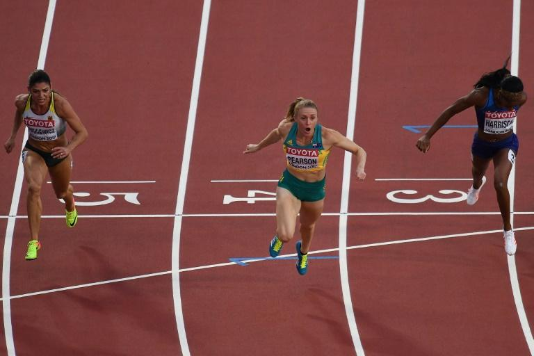 Australia's Sally Pearson (C) reacts after crossing the finish line to win next to US' Kendra Harrison (R) and Germany's Pamela Dutkiewicz (L) in the final of the women's 100m hurdles at the 2017 IAAF World Championships August 12, 2017