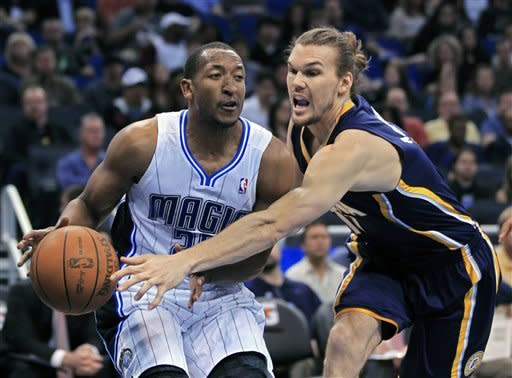 Orlando Magic's Chris Duhon, left, looks to pass the ball as Indiana Pacers' Lou Amundson tries to stop him during the first half of an NBA basketball game Sunday, March 11, 2012, in Orlando, Fla. (AP Photo/John Raoux)