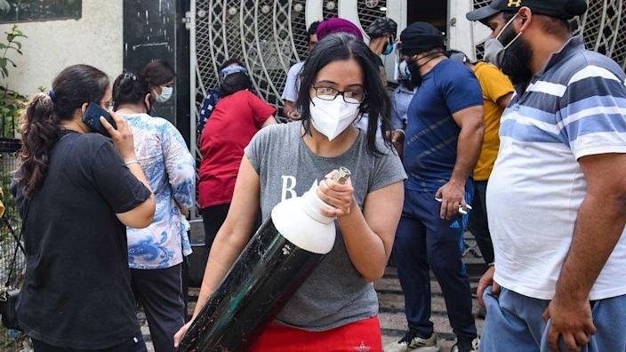 A woman seen with an oxygen cylinder, outside a refilling station at Lajpat Nagar, on May 3, 2021 in New Delhi, India