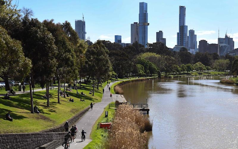People exercise along the banks of the Yarra River in Melbourne - WILLIAM WEST/AFP