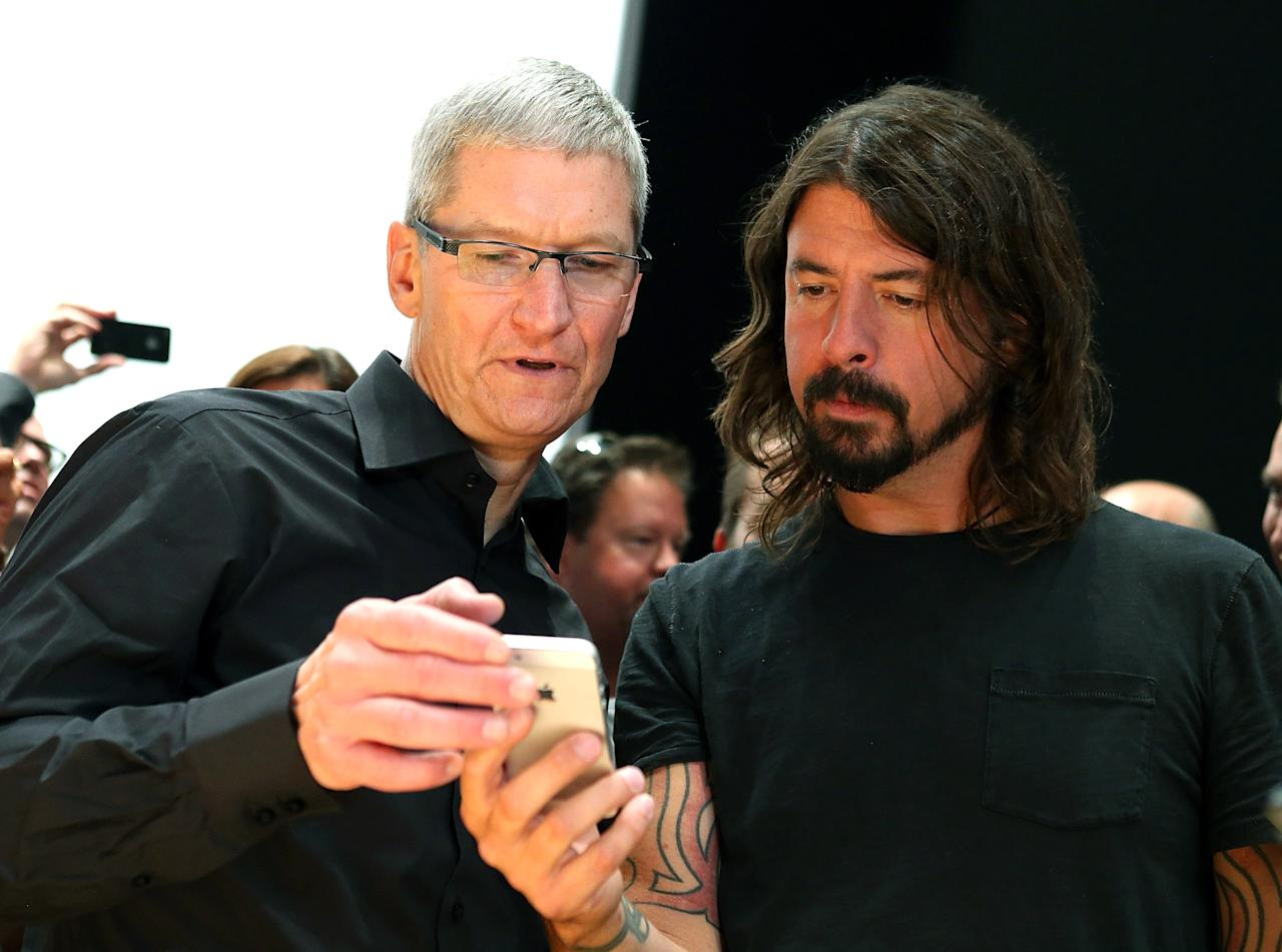 SAN FRANCISCO, CA - SEPTEMBER 12:  Apple CEO Tim Cook (L) and Dave Grohl of the Foo Fighters look at the new iPhone 5 during an Apple special event at the Yerba Buena Center for the Arts on September 12, 2012 in San Francisco, California. Apple announced the iPhone 5, the latest version of the popular smart phone.  (Photo by Justin Sullivan/Getty Images)