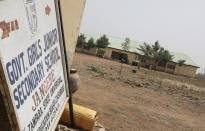 A sign pointos to the Government Girls Junior Secondary School from where more than 300 girls were abducted on Friday by gunmen, in Jangebe town, Zamfara state, northern Nigeria Saturday, Feb. 27, 2021. Nigerian police and the military have begun joint operations to rescue the more than 300 girls who were kidnapped from the boarding school, according to a police spokesman. (AP Photo/Ibrahim Mansur)