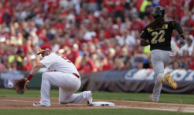 St. Louis Cardinals first baseman Matt Adams (53) fields a low throw as Pittsburgh Pirates' Andrew McCutchen (22) grounds out in the first inning of Game 1 of baseball's National League division series on Thursday, Oct. 3, 2013, in St. Louis. (AP Photo/Charlie Riedel)