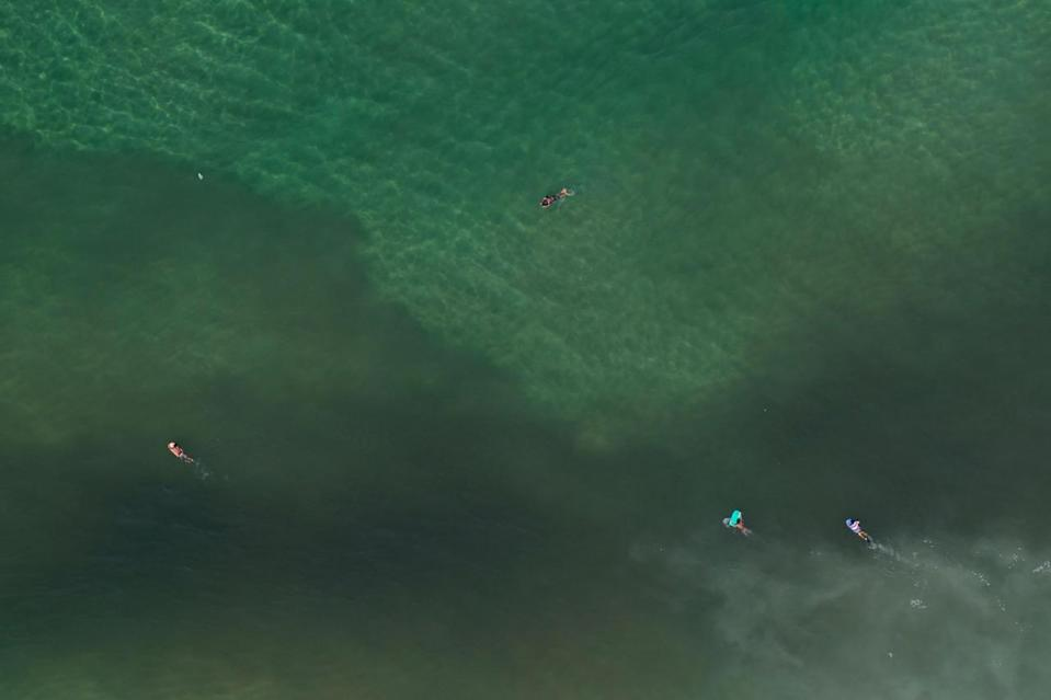 """<p>This July 5, 2016 photo, shows an aerial view of surfers paddling into the polluted waters off Sao Conrado beach in Rio de Janeiro, Brazil. """"It's been decades and I see no improvement,"""" laments biologist Mario Moscatelli, an activist who's the most visible face of the fight to clean up Rio's waterways. Guanabara Bay has been transformed in a latrine … and unfortunately Rio de Janeiro missed the opportunity, maybe the last big opportunity' to clean it up. (AP Photo/Felipe Dana)</p>"""
