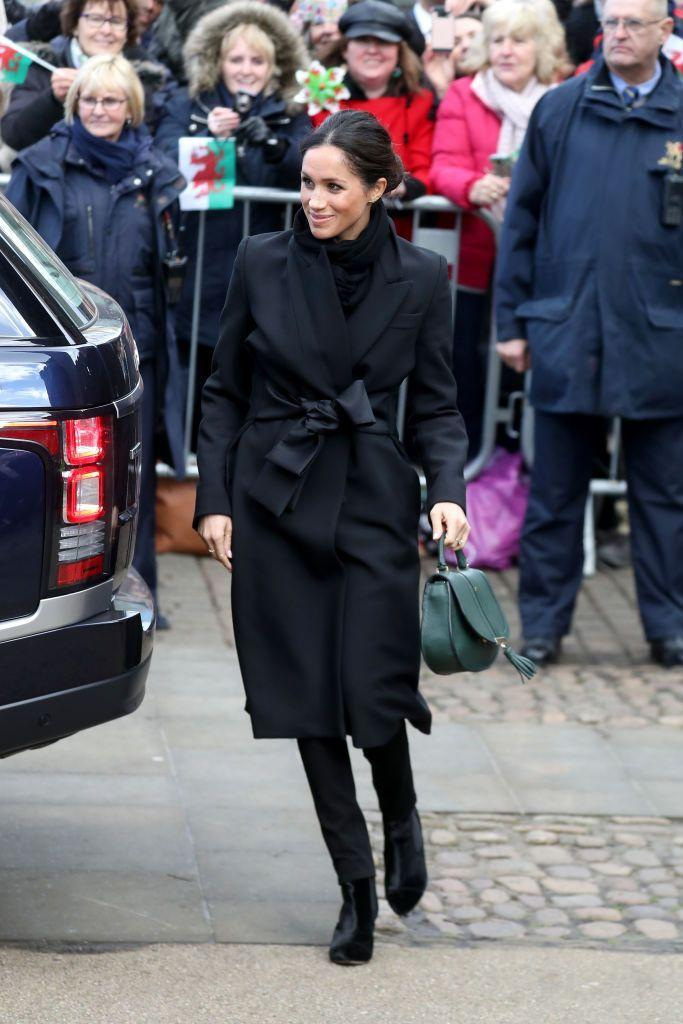 "<p>For her first official visit to Wales, Markle wore an all-black ensemble, <a href=""https://www.harrods.com/en-gb/stella-mccartney/tie-detail-coat-p000000000005808145"" rel=""nofollow noopener"" target=""_blank"" data-ylk=""slk:a Stella McCarney coat"" class=""link rapid-noclick-resp"">a Stella McCarney coat</a>, trousers by Welsh brand Hiut Denim, and <a href=""https://www.demellierlondon.com/the-mini-venice.html"" rel=""nofollow noopener"" target=""_blank"" data-ylk=""slk:a green handbag from DeMellier London"" class=""link rapid-noclick-resp"">a green handbag from DeMellier London</a>.</p>"