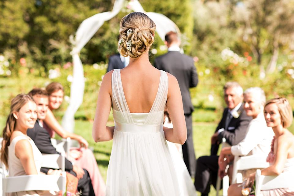 Rear view of young bride walking down the aisle while guests looking at her during wedding ceremony. Horizontal shot.