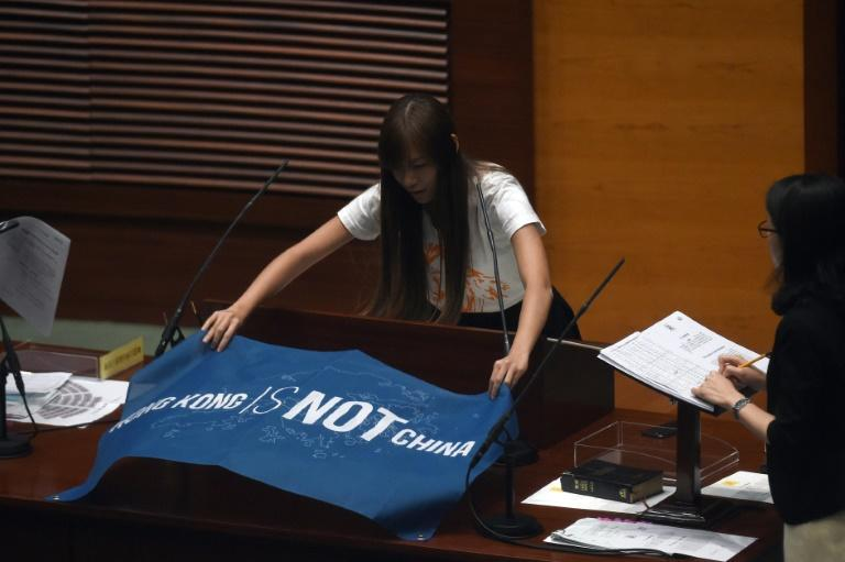 """Yau Wai-ching displays a banner reading """"Hong Kong is not China"""" before taking the Legislative Council Oath in 2016"""