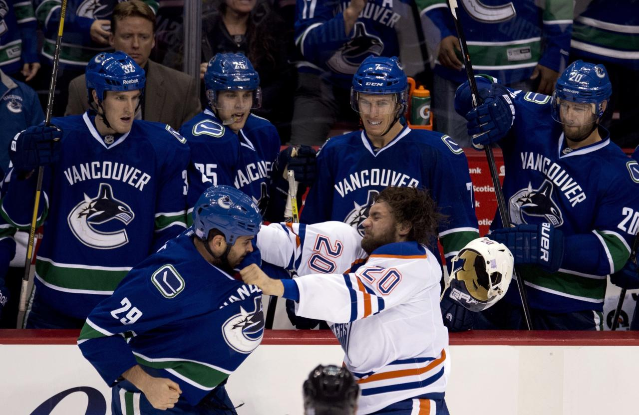 Vancouver Canucks left wing Tom Sestito (29) and Edmonton Oilers left wing Luke Gazdic (20) get into a fight during the third period of NHL hockey action in Vancouver, British Columbia, Saturday, Oct. 5, 2013. (AP Photo/The Canadian Press, Jonathan Hayward)