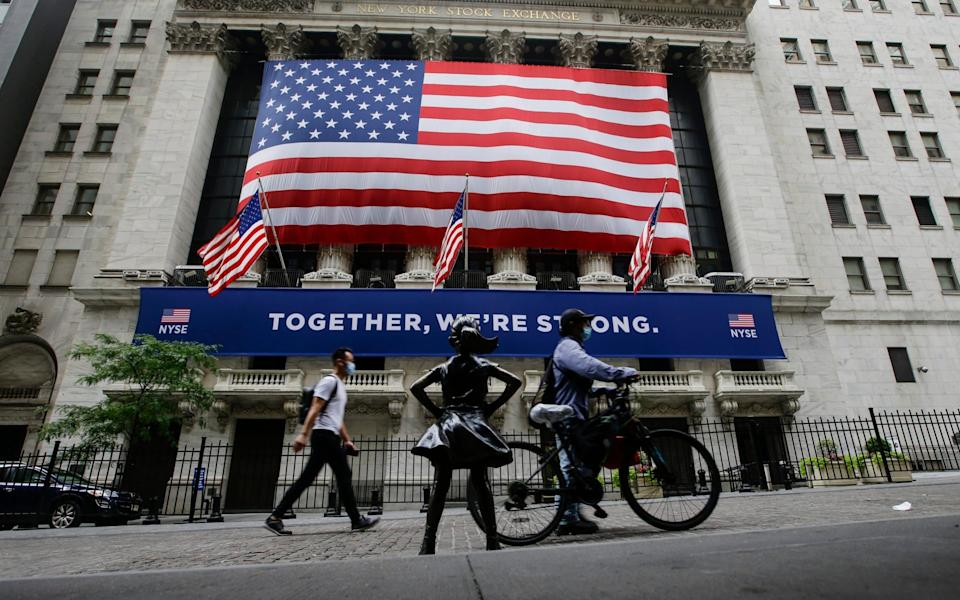 Pedestrians wearing protective masks during the coronavirus pandemic pass by the New York Stock Exchange - AP