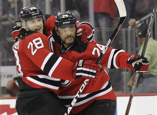 New Jersey Devils' Bryce Salvador, right, celebrates with Anton Volchenkov, of Russia, after scoring in the second period during Game 5 of the NHL hockey Stanley Cup finals, Saturday, June 9, 2012, in Newark, N.J.. (AP Photo/Julio Cortez)