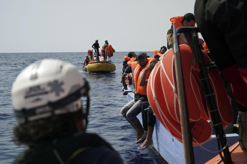 Migrants listen to SOS Mediterranee staff during a rescue operation some 53 nautical miles (98 kilometers) from the coast of Libya in the Mediterranean Sea, Tuesday, Sept. 17, 2019. The humanitarian rescue ship Ocean Viking pulled 48 people from a small and overcrowded wooden boat including a newborn and a pregnant woman. (AP Photo/Renata Brito)