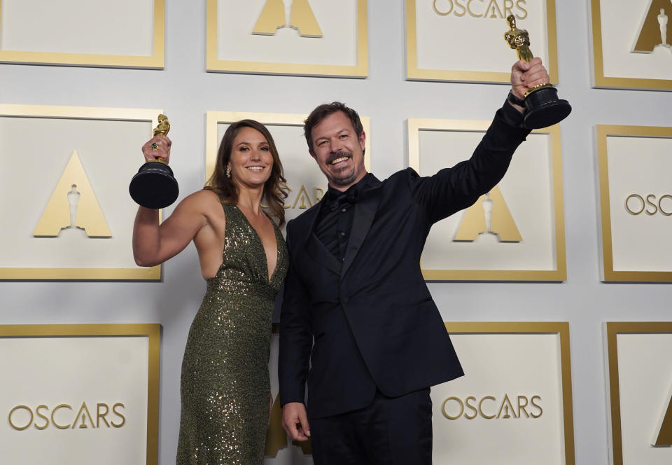 """Pippa Ehrlich, left, and James Reed pose in the press room with the award for best documentary feature for """"My Octopus Teacher"""" at the Oscars on Sunday, April 25, 2021, at Union Station in Los Angeles. (AP Photo/Chris Pizzello, Pool)"""