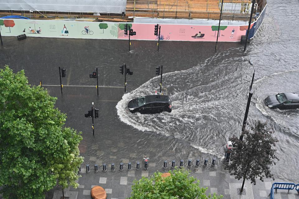 Cars drive through deep water on a flooded road in The Nine Elms district of London on July 25, 2021 during heavy rain. - Buses and cars were left stranded when roads across London flooded on Sunday, as repeated thunderstorms battered the British capital. (Photo by JUSTIN TALLIS / AFP) (Photo by JUSTIN TALLIS/AFP via Getty Images)