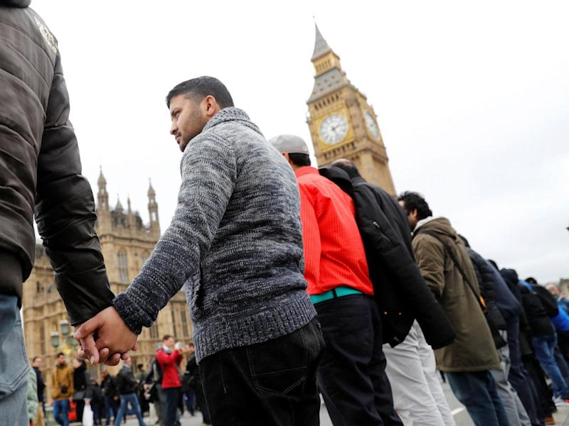 People hold hands on Westminster Bridge during an event to mark one week since the Westminster attack on 29 March (Reuters)