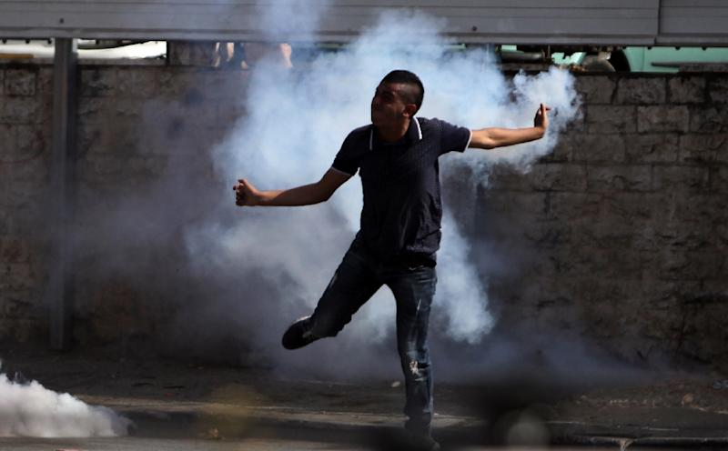 A Palestinian youth runs through tear gas during clashes with Israeli soldiers in al-Ram, near Ramallah, following a protest after security forces entered the al-Aqsa mosque compound in Jerusalem on September 15, 2015 (AFP Photo/Abbas Momani)