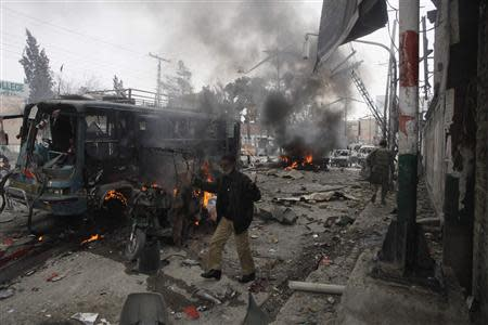 A policeman calls for help as he stands near a burning site after a bomb blast in Quetta
