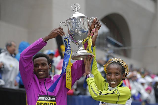 Men's division winner Lelisa Desisa of Ethiopia (L) and women's division winner Caroline Rotich of Kenya pose with the trophy at the finish line of the 119th Boston Marathon in Boston, Massachusetts April 20, 2015. REUTERS/Brian Snyder TPX IMAGES OF THE DAY