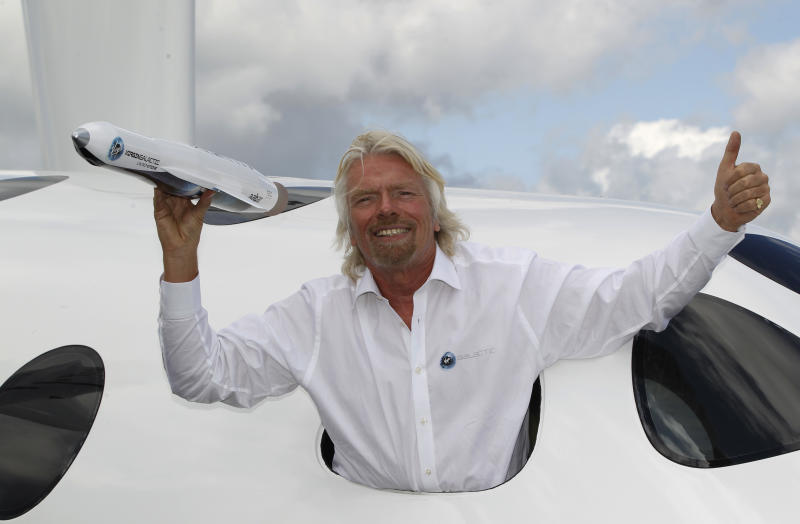 Sir Richard Branson poses for the photographers in the window of a replica of the Virgin Galactic, which according to the company will be the world's first commercial spaceline, at the Farnborough International Airshow in Farnborough, England, Wednesday, July 11, 2012. Branson also revealed a plan to launch small satellites into space at a tenth of the current cost. (AP Photo/Lefteris Pitarakis)
