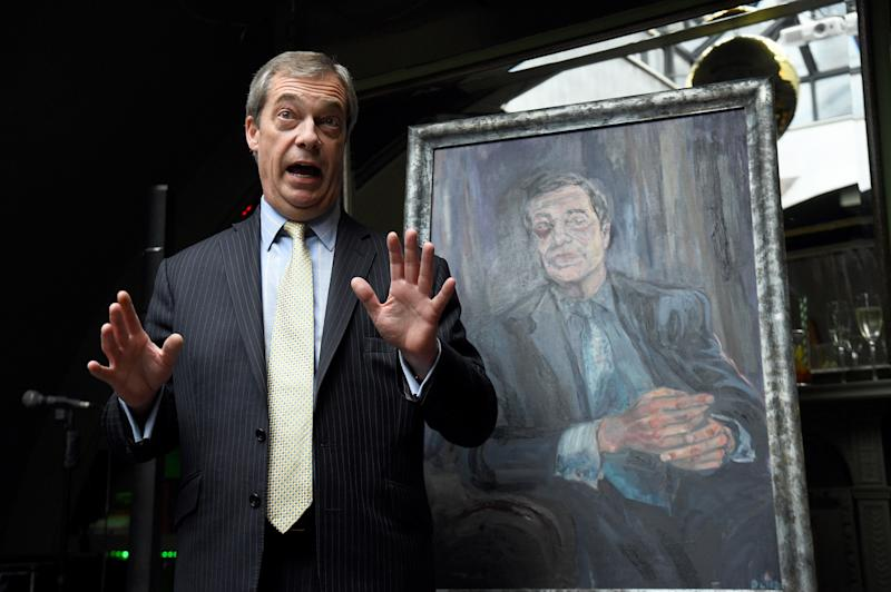 Nigel Farage stands beside a portrait of himself titled Mr Brexit, by artist Dan Llywelyn Hall, at L'Escargot Restaurant in London.