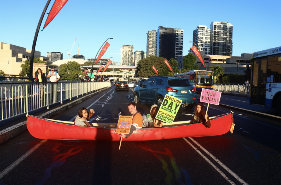 The four protestors in the canoe on Thursday morning on Victoria Bridge, Brisbane.