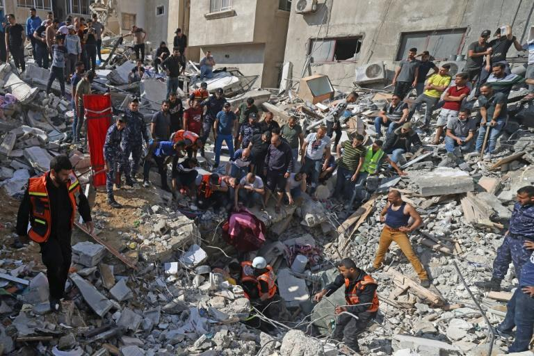 Palestinian paramedics search for survivors under the rubble of a destroyed building in Gaza City
