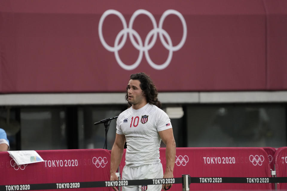 Madison Hughes of the United States walks past the Olympic Rings after his team lost to Britain during their men's rugby sevens quarterfinal match at the 2020 Summer Olympics, Tuesday, July 27, 2021, in Tokyo. (AP Photo/Shuji Kajiyama)