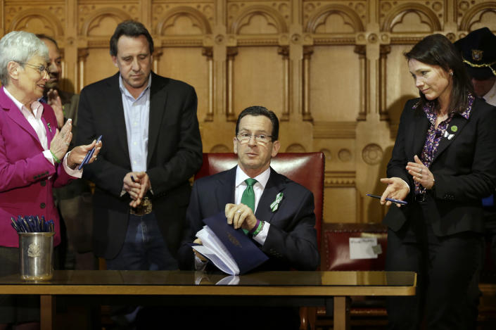 Connecticut Gov. Dannel P. Malloy, center, completes signing legislation at the Capitol in Hartford, Conn., Thursday, April 4, 2013, that includes new restrictions on weapons and large capacity ammunition magazines, a response to last year's deadly school shooting in Newtown. Neil Heslin, second from left, father of Sandy Hook shooting victim Jesse Lewis, Nicole Hockley, right, mother of Sandy Hook School shooting victim Dylan, and Conn. Lt. Gov. Nancy Wyman, left, applaud. The legislation adds more than 100 firearms to the state's assault weapons ban, sets eligibility rules for buying ammunition, and creates what officials have called the nation's first dangerous weapon offender registry. (AP Photo/Steven Senne)