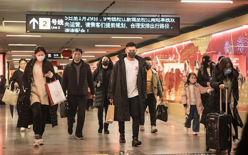Commuters wearing protective masks walk through a subway station ahead of the Lunar New Year in Shanghai - Bloomberg
