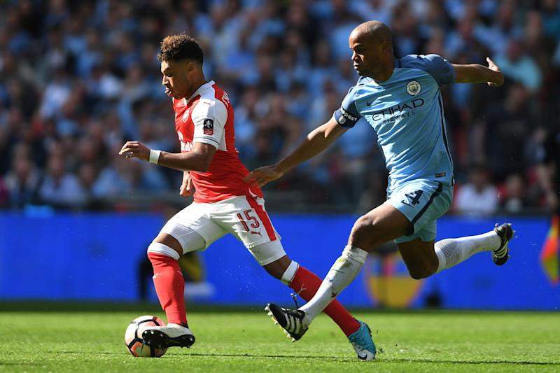 Alex Oxlade-Chamberlain of Arsenal and Vincent Kompany of Manchester City compete for the ball during the Emirates FA Cup Semi-Final match between Arsenal and Manchester City at Wembley Stadium