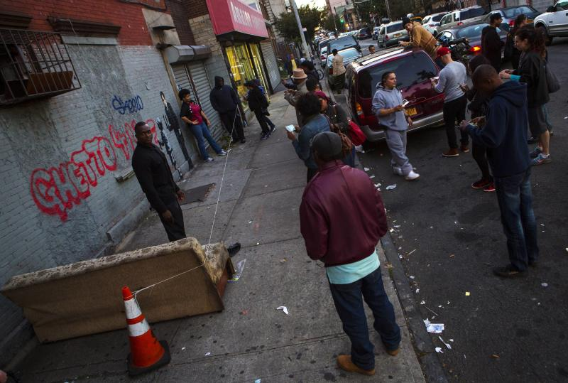 People gather near an installation by British graffiti artist Banksy in the Bronx section of New York