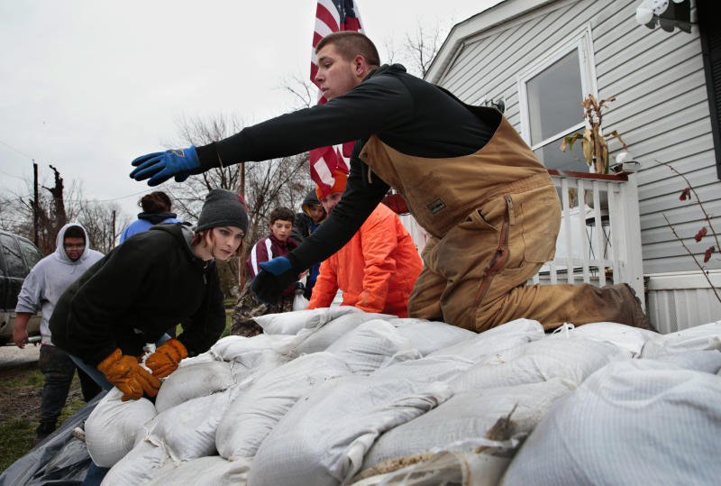 Sky Coleman, left, stacks a sandbag as Tyler Hopkins awaits another as a group of 15 middle and high school students from the nearby city of Louisiana, Mo., sandbagged the home of the aunt of a fellow student in Clarksville, Mo., Saturday, March 30, 2019. The Mississippi River reached 32.8 feet Saturday afternoon, entering major flood stage for the first time this spring. It is expected to crest late Sunday at 34.2 feet, more than three feet below the 37.7 foot record of 1993. (Robert Cohen/St. Louis Post-Dispatch via AP)
