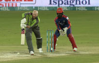 Qalandars batsman Ben Dunk, left, plays a shot while Karachi Kings wicketkeeper Chadwick Walton watches during the final of Pakistan Super League T20 cricket match at National Stadium in Karachi, Pakistan, Tuesday, Nov. 17, 2020. (AP Photo/Fareed Khan)