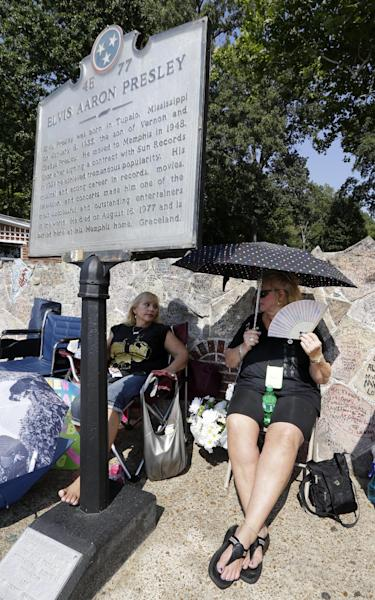 Elvis Presley fans Cheryl Skogen, left, and Susan Struss, both from Los Angeles, wait in line outside Graceland, Presley's Memphis, Tenn. home, on Wednesday, Aug. 15, 2012. Fans are lined up to take part in the annual candlelight vigil marking the 35th anniversary of Presley's death. (AP Photo/Mark Humphrey)