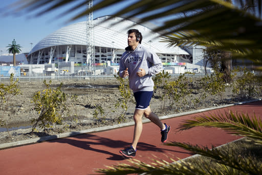 A man runs at a boardwalk near the Fisht Olympic Stadium in Olympic Park during the 2014 Winter Olympics, Monday, Feb. 10, 2014, in Sochi, Russia. (AP Photo/Pavel Golovkin)