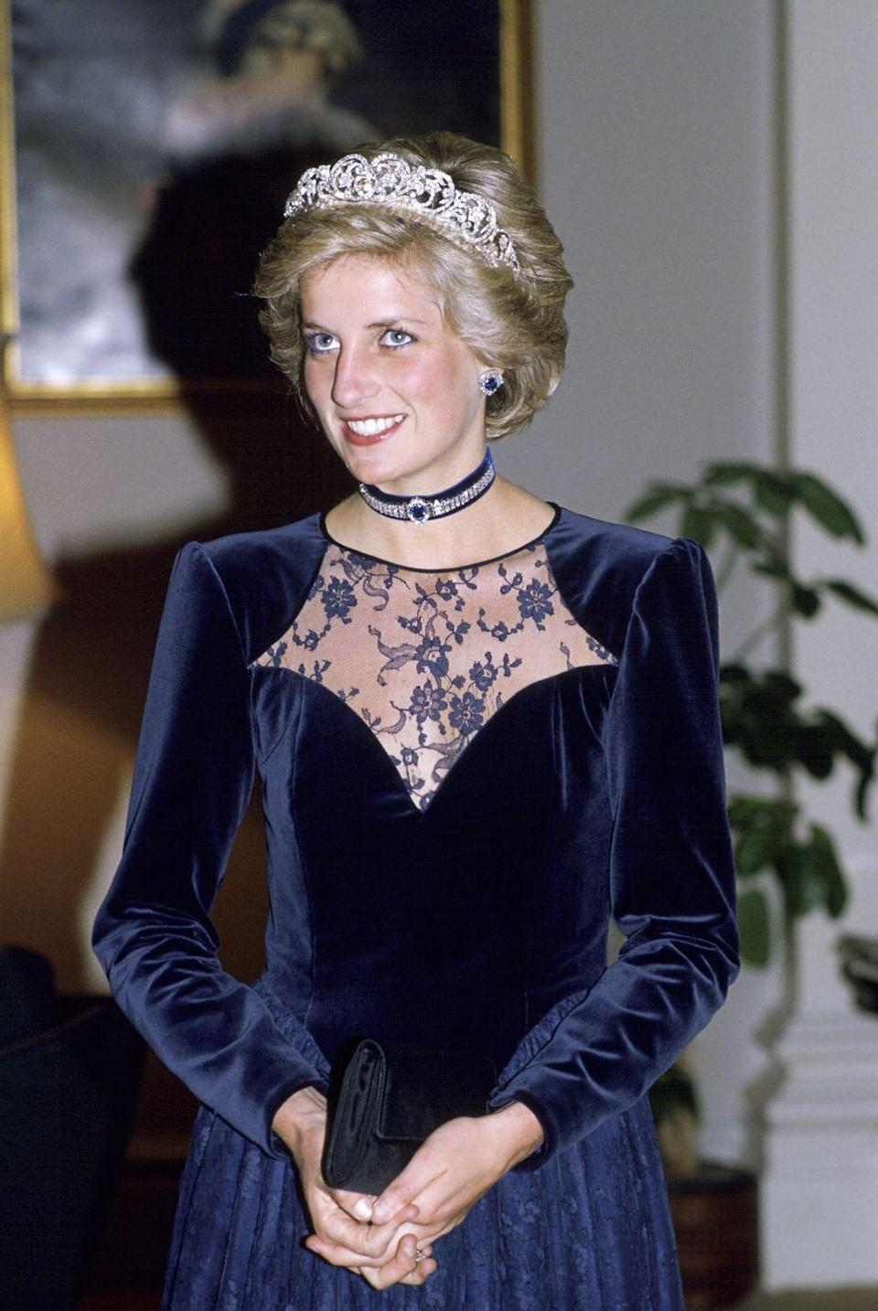 <p>Princess Diana opted for shades of navy blue at a state dinner in Melbourne, Australia. The princess chose a navy velvet gown with lace detailing, a choker necklace and earrings from the sapphire and diamond Saudi suite, and the Spencer tiara. </p>
