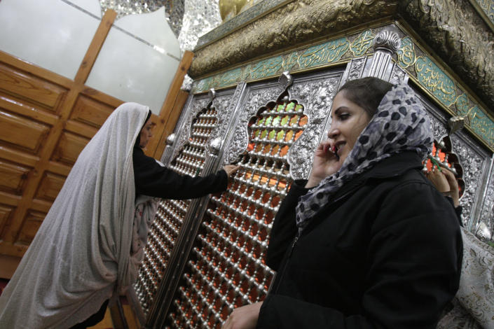 In this picture taken on Thursday, Feb. 16, 2012, a Jewish Iranian woman, right, talks on her cell phone during her pray at the tomb of biblical prophet Daniel, in the city of Susa, some 450 miles ( 750 kilometers) southwest of the capital Tehran, Iran. All but lost amid the heated talk about a possible Israeli attack on Iran's suspect nuclear program are the thousands of Jews who live in the Islamic Republic and could be caught in the middle. (AP Photo/Vahid Salemi)