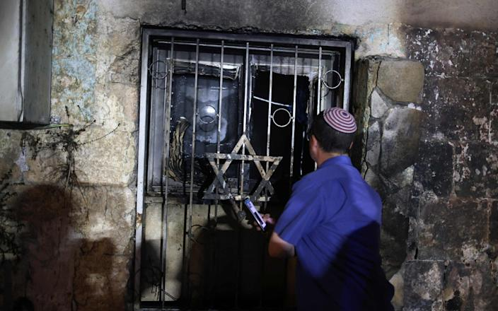 An Israeli man looks inside a synagogue, after it was set on fire by Arab-Israelis, in the mixed Jewish-Arab city of Lod - AFP