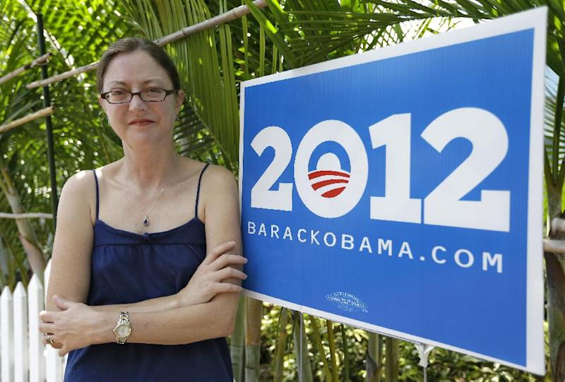 In this photo taken Oct. 9, 2012, Photo, Erin Mitchell poses with a President Obama campaign sign at her home in St. Petersburg, Fla. Which way Florida swings in presidential elections is largely due to the transient nature of its population. A constant influx of new residents, like Mitchell, can make a difference from one election cycle to the next. Mitchell moved to Florida from Boston and had lived in Chicago before that. She used to be a Democrat, then registered as a Republican and is now an independent. She voted for Republican George W. Bush in 2000, but went for Democrats John Kerry in 2004 and Barack Obama in 2008. (AP Photo/Chris O'Meara)