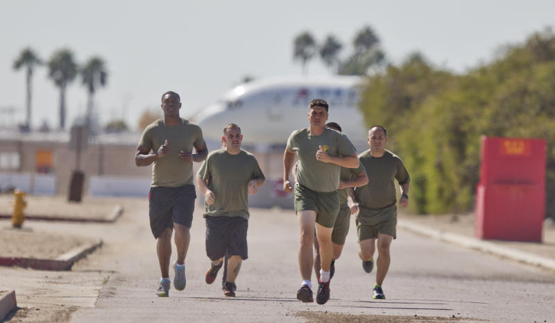"In a Thursday, Oct. 17, 2013 photo, a group of sailors and Marines who failed the so-called ""tape test'' are led by an instructor on a three mile run as they work to improve their fitness and remain in the military, at the Marine Corps Recruit Depot in San Diego. Doctors say a number of military personnel are turning to liposuction to remove excess fat from around the waist so they can pass the Pentagon's body fat test. Some service members say they have no other choice because the Defense Department's method of estimating body fat is weeding out not just flabby physiques but bulkier, muscular builds. A number of fitness experts and doctors agree, and they're calling for the military's fitness standards to be revamped. (AP Photo/Lenny Ignelzi)"