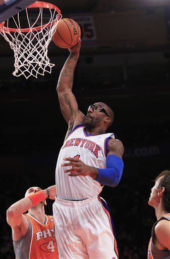 New York Knicks' Amare Stoudemire (1) dunks the ball on Phoenix Suns' Marcin Gortat (4), of Poland, during the first half of an NBA basketball game on Wednesday, Jan. 18, 2012, in New York. (AP Photo/Frank Franklin II)