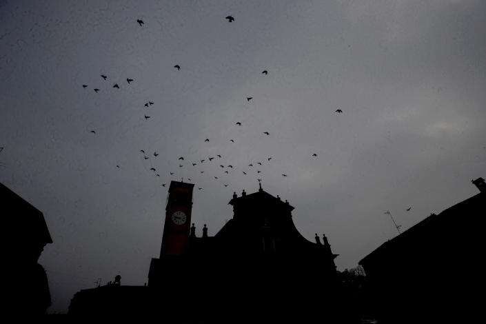 Birds fly over the San Biagio church in Codogno, northern Italy, Sunday, Feb. 21, 2021. Italians are marking one year since their country experienced the first known locally transmitted COVID-19 case in the West. With church services Sunday and wreath-laying ceremonies, including in small northern towns which were the first to be hard-hit by the pandemic, residents paid tribute to the dead. (AP Photo/Luca Bruno)